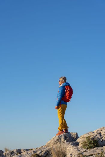 Low angle view of boy standing on rock against clear blue sky