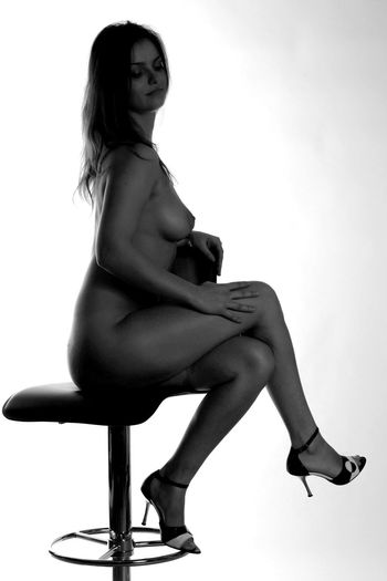 Woman sitting on seat against white background