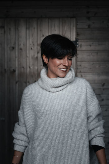 Smiling woman standing against wall in winter