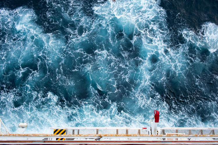 Lifeboat launching appliance from upper view on cruise ship with splashing waves in deep blue sea