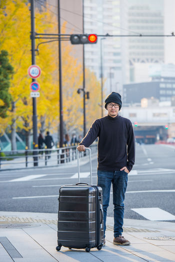 Portrait Of Man With Wheeled Luggage Standing On Sidewalk In City During Autumn