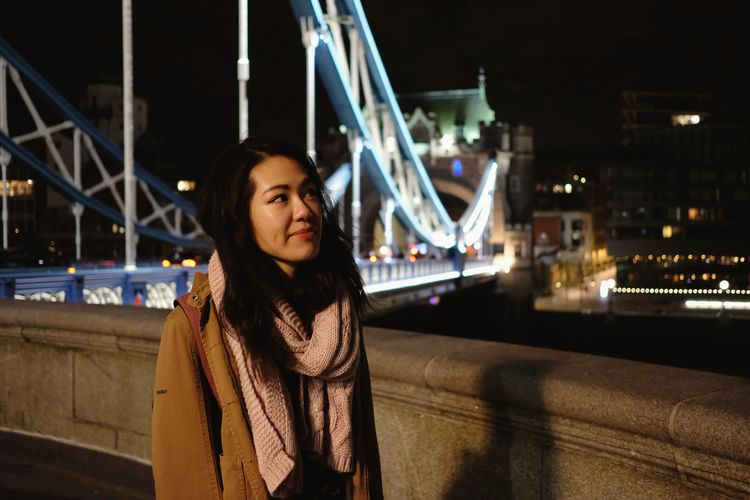 Young woman standing against illuminated bridge at night