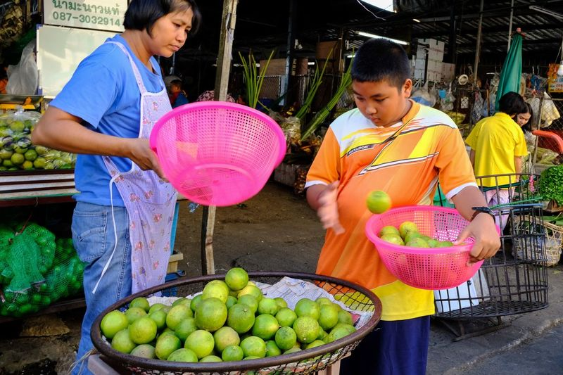 Teenage boy buying oranges from vendor at market stall