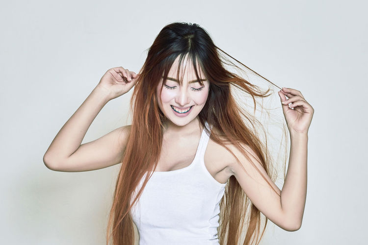 Adult Beautiful Woman Cheerful Day Front View Hand In Hair Happiness Long Hair Looking At Camera One Person People Portrait Real People Smiling Studio Shot Tank Top White Background Young Adult Young Women