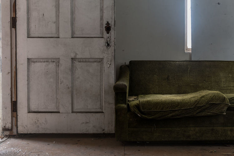 Empty weathered sofa by open door of abandoned home