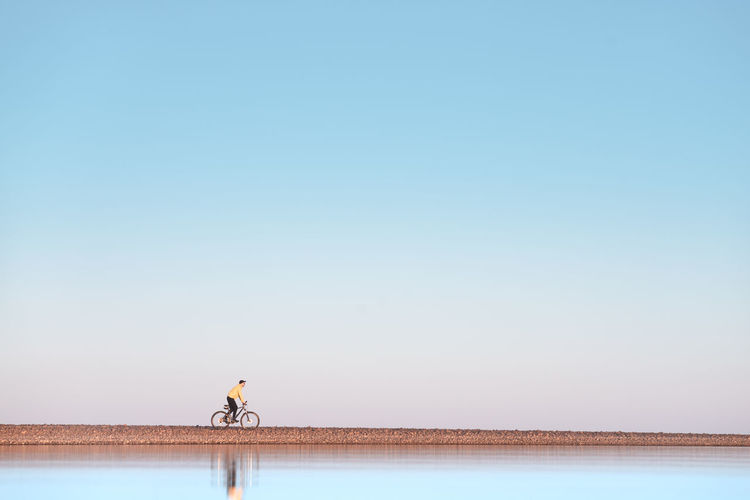 A cyclist rides on a stone spit. the view from the water.