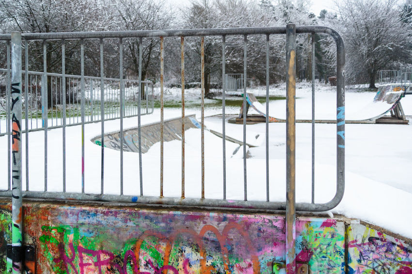 View through railings at the top of the ramp in a snow covered deserted skatepark in winter. Blanket Of Snow Graffiti Shades Of Winter Skatepark Trees Winter Day Geometry Nature No People Outdoors Railings Snow Snow Covered Urban