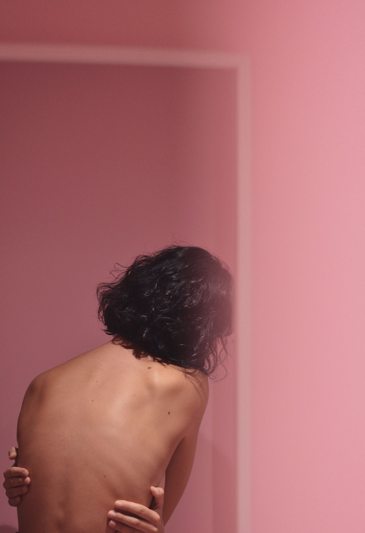Rear view of shirtless sensuous woman standing against pink wall