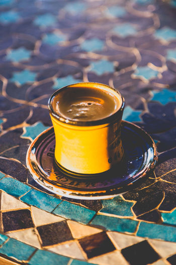 Strong dark roasted arabic coffee in traditional small yellow ceramic cup on mosaic table in Moroccan restaurant. Close up vertical shot. Arabic Coffee Circle Espresso One Shot Paint The Town Yellow Square And Circle Strong Coffee Stylish Tasty Drink Afternoon Coffee Aromatic Blue And Yellow Ceramic Cup Close Up Energy Evening Golden Light Islamic Keeping Awake Modest Mosaic Table Restaurant Table Round Traditional Food Yellow Color