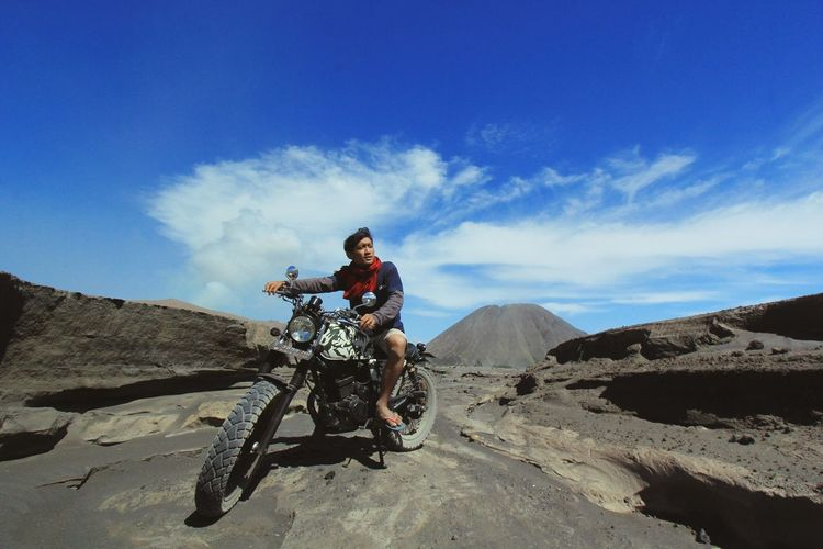 Young man riding motorcycle on desert against blue sky