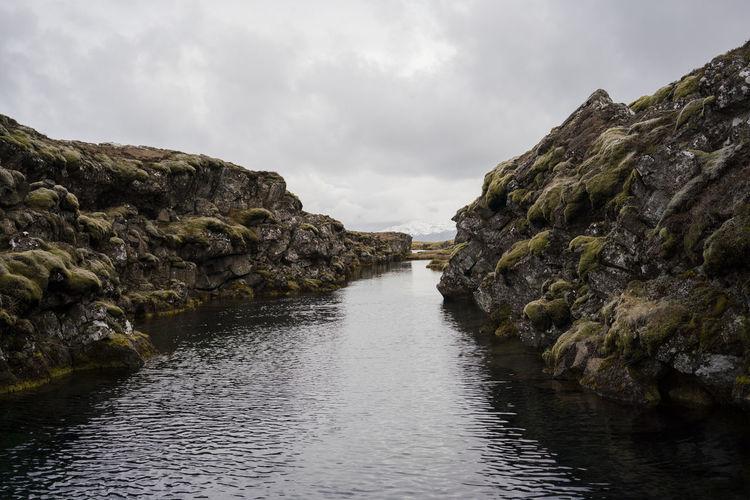 River amidst rocks against sky