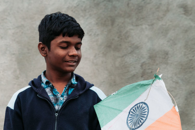 Smiling boy holding kite standing against wall