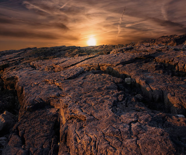 Rock formations on land against sky during sunset