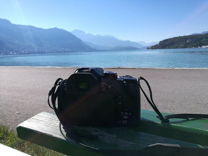 Digital camera on bench at lakeshore against clear blue sky