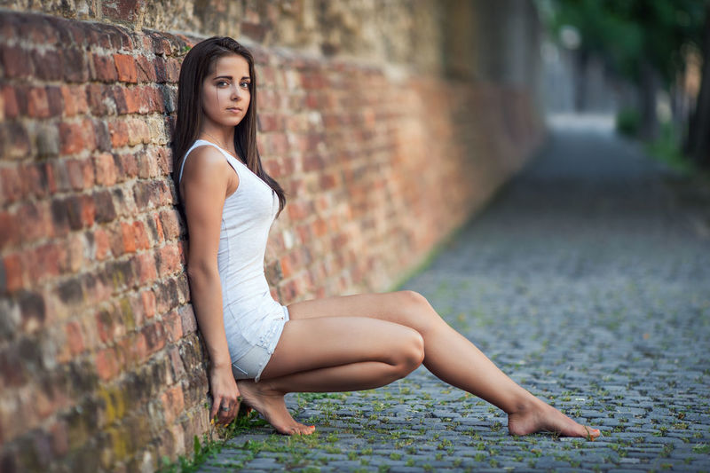 Portrait Of Young Woman Leaning On Brick Wall