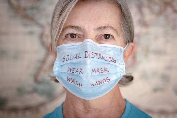 Close-up portrait of woman wearing mask with text