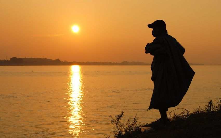 Silhouette of a person at the edge of the lake