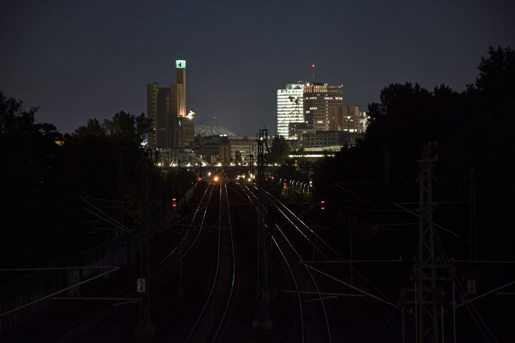 High angle view of railroad tracks leading to illuminated buildings in city