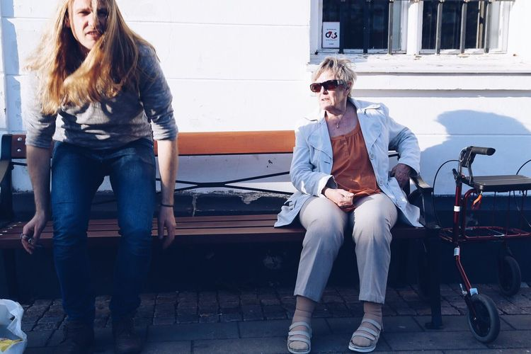Woman Looking At Man While Sitting On Bench