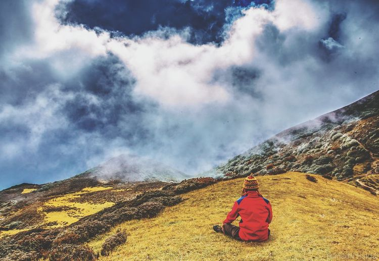 Rear View Of Man Sitting On Mountain Against Cloudy Sky