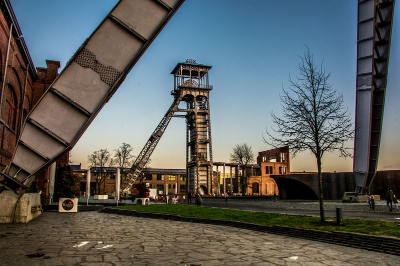 C-Mine Genk is a old mining facility which is turned in to a cultural place with a cinema, school of arts and several restaurants and bistro's Belgie Belgium Coal Coalmine Genk Illuminated Industrial Industry Licht Light Limburg Mijn Mine Mining Heritage No People Outdoors Schacht Sky Sun Sunlight Sunset Toren Tower Towers Zwarte Goud