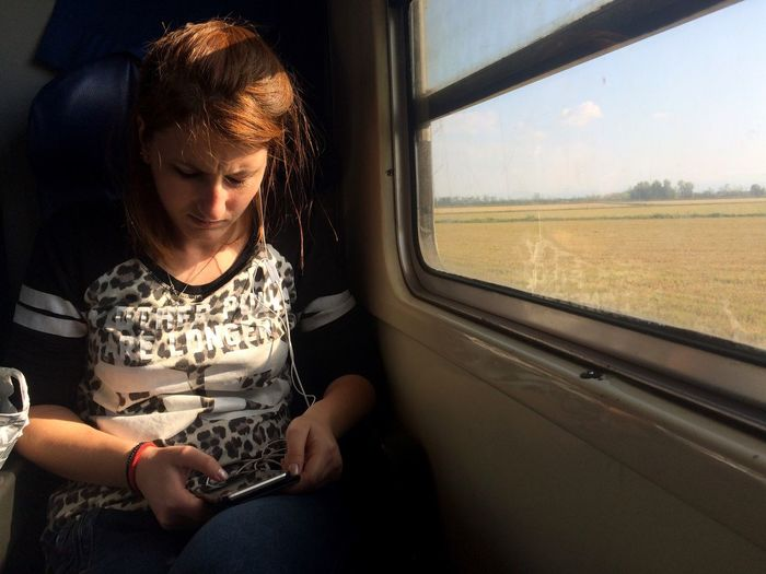 Woman using phone while sitting in train