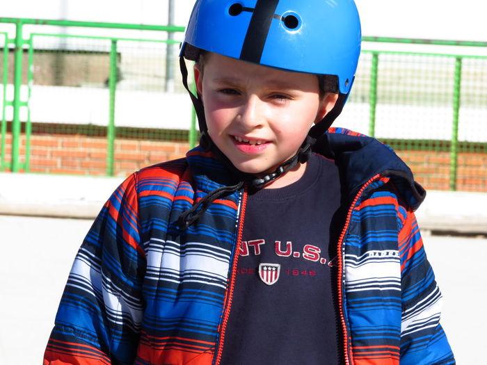 Portrait of boy wearing sports helmet standing at skateboard park