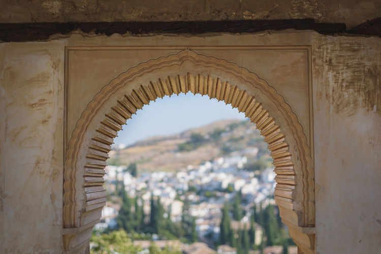 Landscape with buildings shot through an arch in a historical building in the Alhambra in Granada, Spain. Alhambra De Granada  Ancient Architecture Granada Moorish Architecture SPAIN Travel Alhambra Ancient Architecture Arch Building Buildings Landscape Moorish Old Shot Through Stone Summer Through Travel Destinations