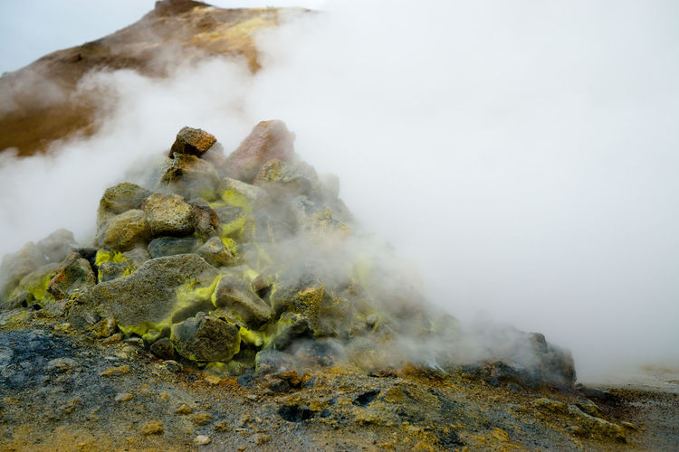 Rocks Pile Amidst Smoke In Volcanic Crater