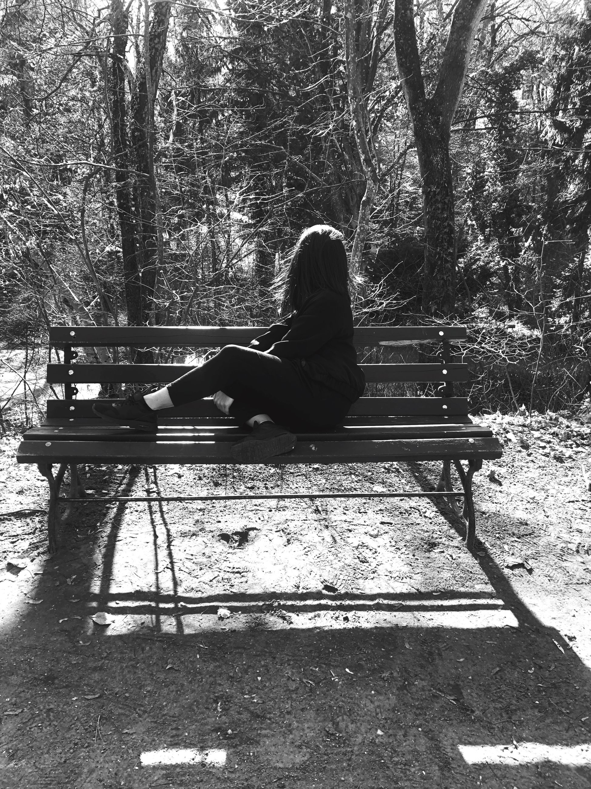 sitting, one person, tree, bench, full length, real people, leisure activity, lifestyles, plant, nature, park, day, relaxation, seat, women, adult, park - man made space, outdoors, casual clothing, park bench, contemplation, hairstyle, warm clothing