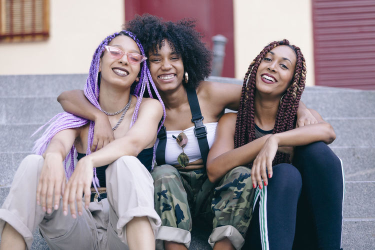 Portrait of smiling female friends sitting on steps