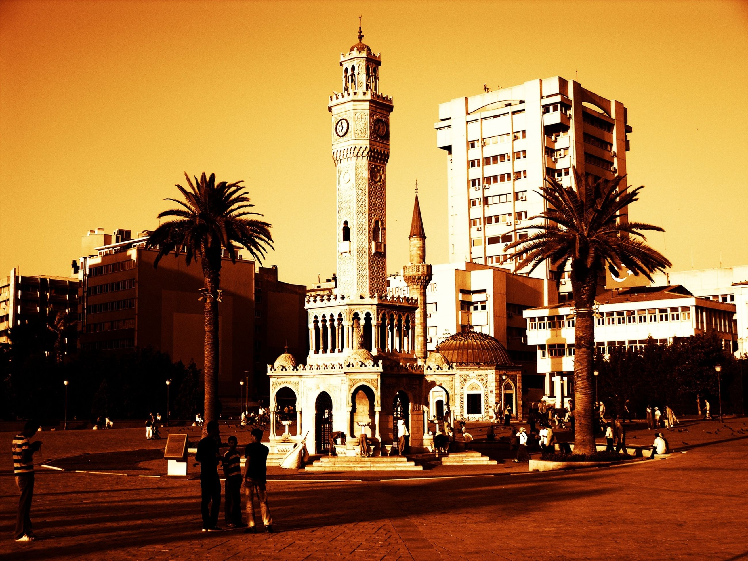 building exterior, architecture, built structure, city, street, palm tree, sunset, tree, tall - high, city life, building, sky, tower, incidental people, street light, city street, clear sky, road, travel destinations, residential building