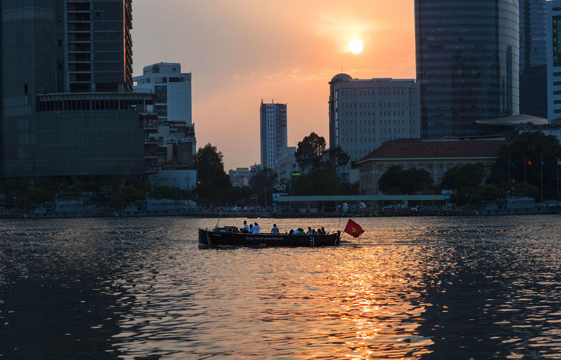 Boat sailing on river in city against sky during sunset