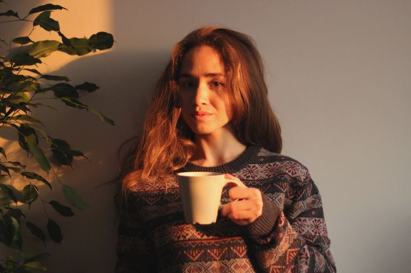 One Person Cup Drink Young Adult Mug Coffee Cup Portrait Young Women Coffee Refreshment Lifestyles Adult Coffee - Drink Looking Away Food And Drink Contemplation Indoors  Warm Clothing Drinking Hot Drink This Is My Skin Adventures In The City