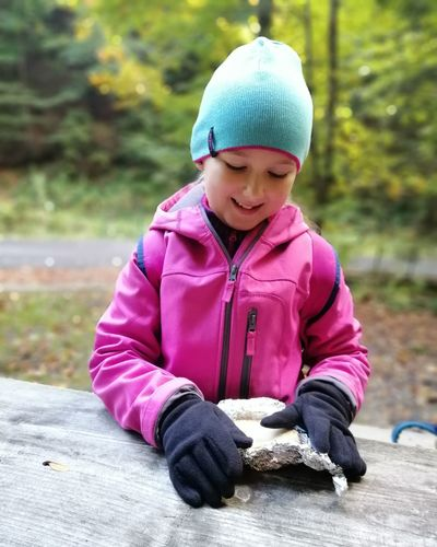 Cute smiling girl holding rock on table while standing against trees in forest