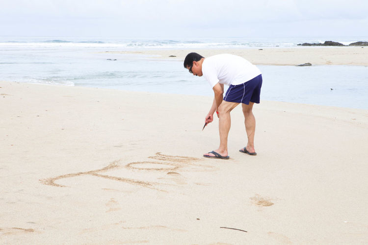 Full length side view of man writing in sand at beach