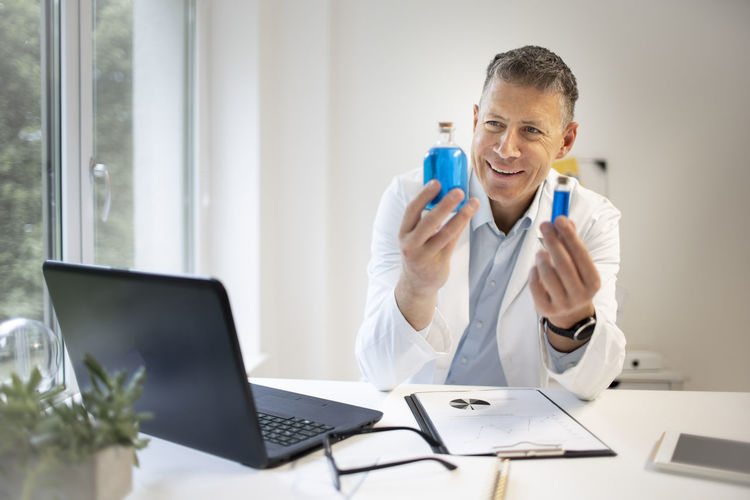 Mid adult man using mobile phone while sitting on table