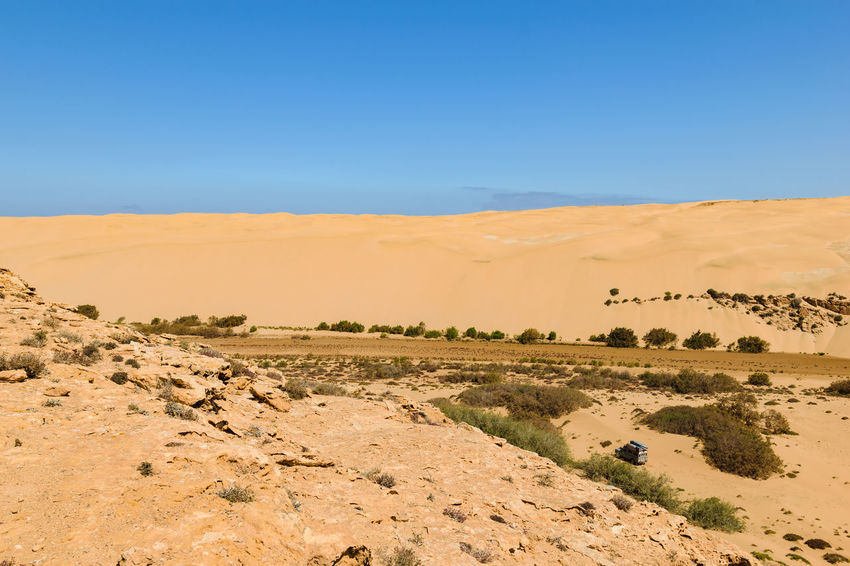 Image of an off-road car in the Oued Aoreora which is the entry to the piste Plage Blanche, Morocco. 4wd 4x4 Camping Desert Morocco Nature Off-Road Oued River View Riverbed SUV Travel Adventure Africa Aoreora Arid Climate Blue Car Dry Landscape Outdoor Safari Sahara Vehicle