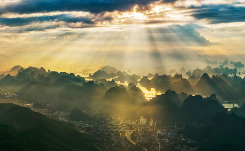 Sunlight streaming through clouds on halong bay during sunrise