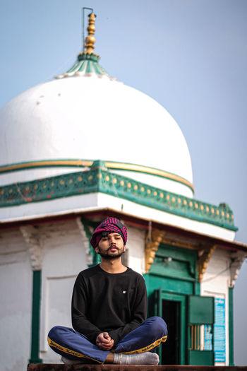 Portrait of man sitting against temple against sky