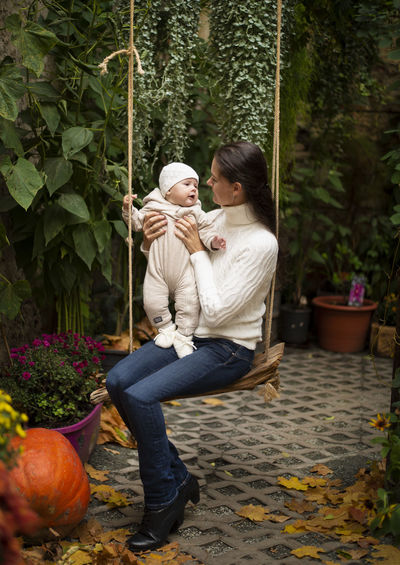 Mother and daughter sitting on swing by plants