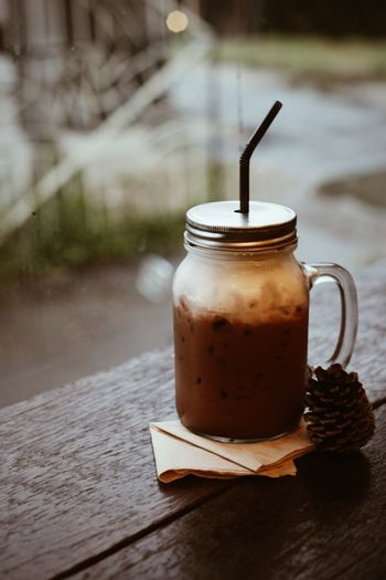 Chocolate drink in container by pine cone on table