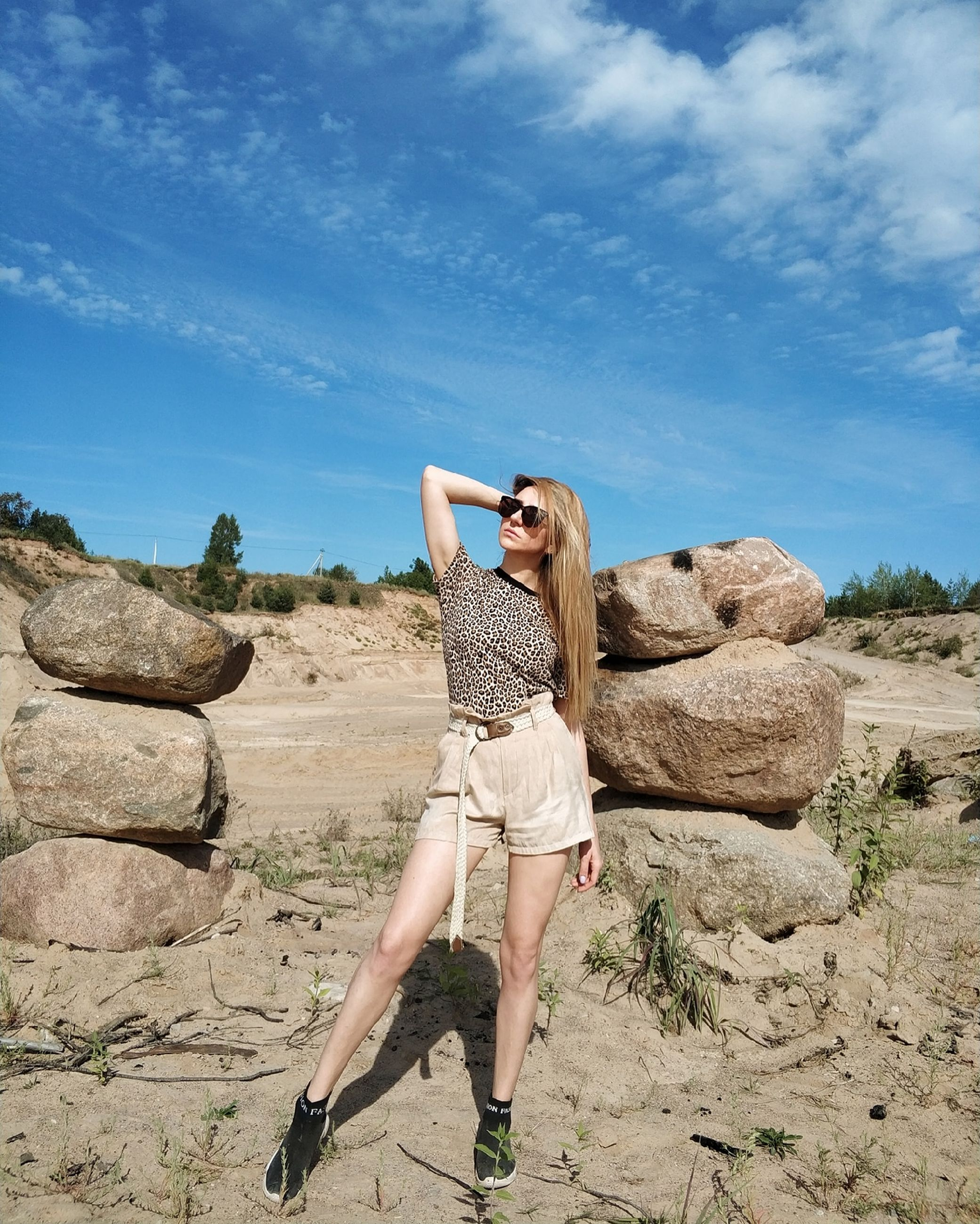 one person, leisure activity, real people, lifestyles, young adult, young women, solid, nature, full length, casual clothing, day, standing, rock, sky, rock - object, women, adult, sunlight, outdoors