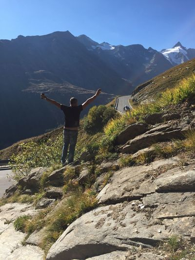Rear view of man with arms outstretched standing on rock by road against mountains