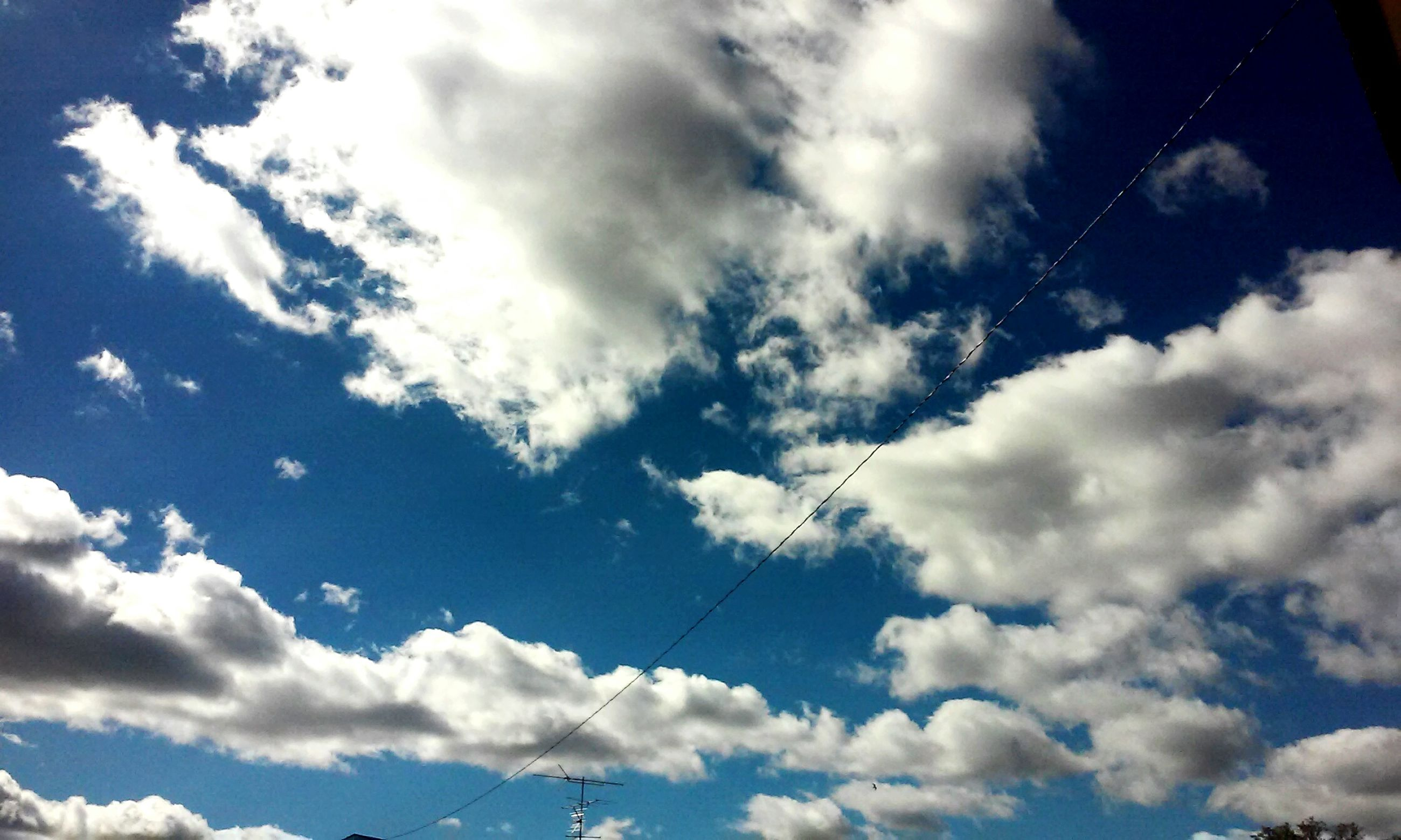 low angle view, blue, sky, scenics, tranquility, tranquil scene, beauty in nature, cloud, cloud - sky, white, day, nature, majestic, sky only, outdoors, cloudscape, cloudy, heaven, power line, no people, atmosphere, non-urban scene