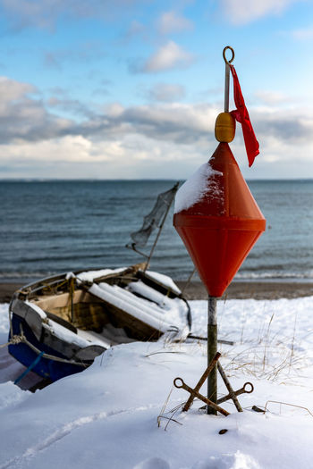 Clothes hanging on snow covered land against sea