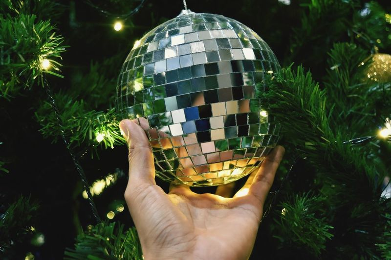 Close-Up Of Hand Holding Disco Ball On Illuminated Christmas Tree At Night