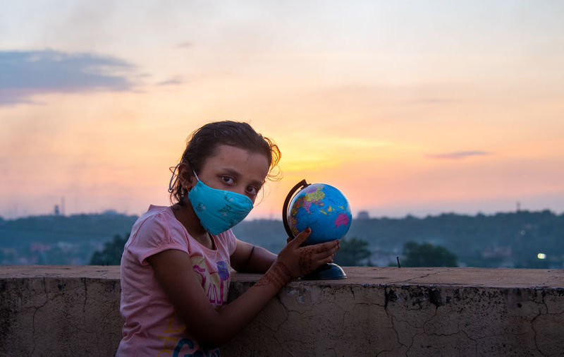 Portrait of girl holding man made globe against sky during sunset
