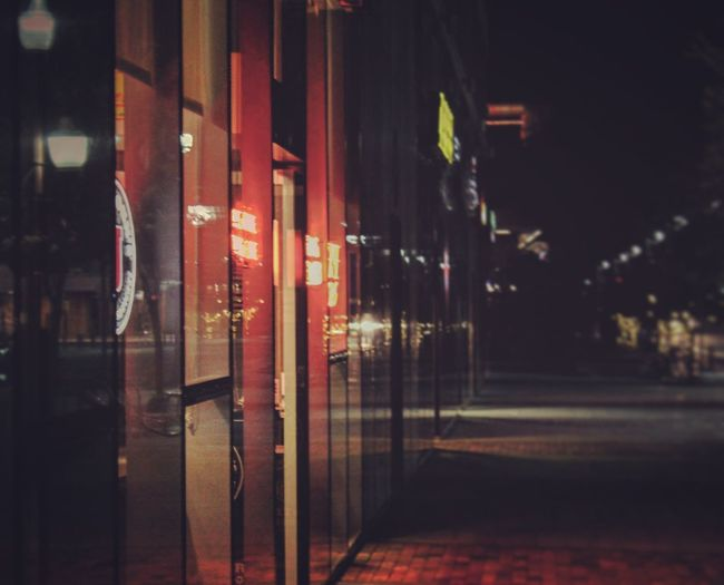 Illuminated street by building at night