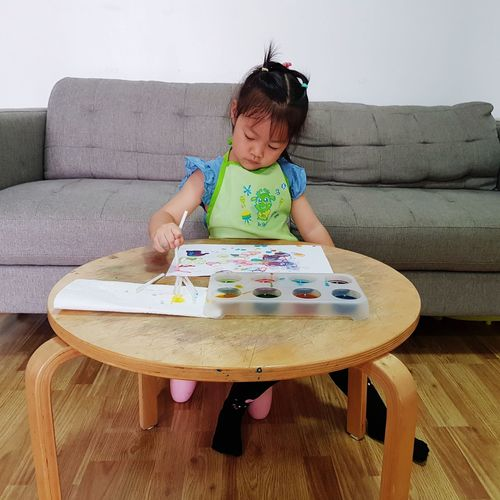 Girl painting while sitting on sofa at home